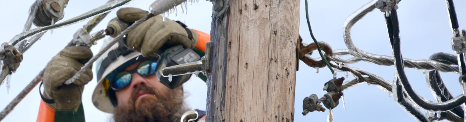 Photograph of lineworker fixing power lines.